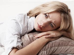 woman-looking-sad-on-pillow